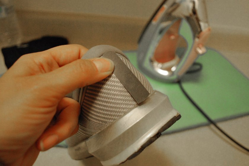 Step 2:  Place the strip on the area you want reflection. This was tricky for me because of my shoe's convex shape at the heel. Be very careful when ironing on these rounded surfaces. Gently, I ironed the bottom of the strip first then the top for 30-60 seconds. Not seen is the paper towel I placed in between the strip and iron.